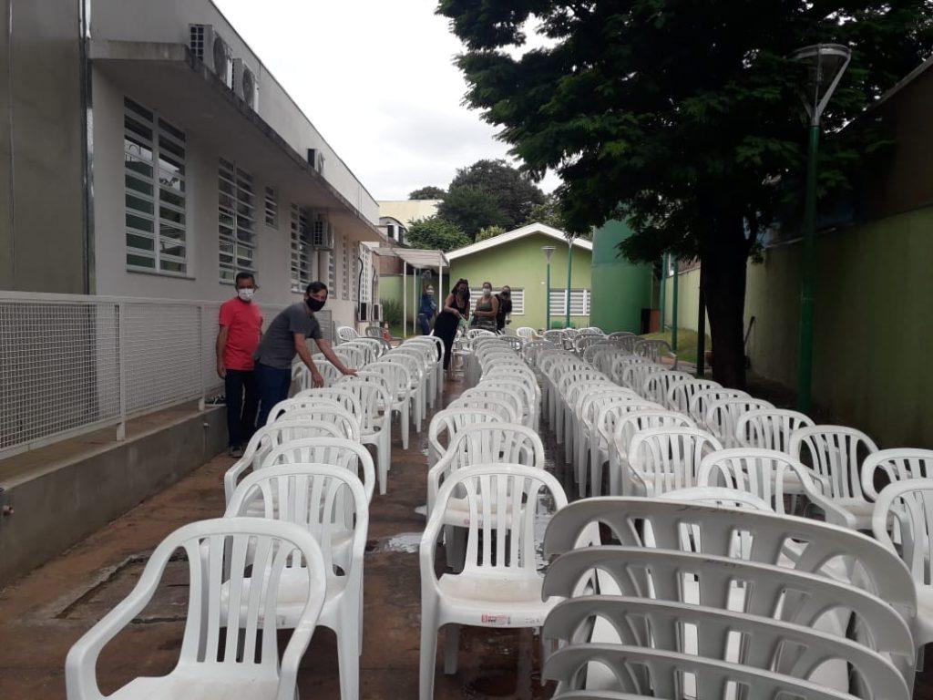 Voluntários da Prefeitura levam cadeiras para idosos